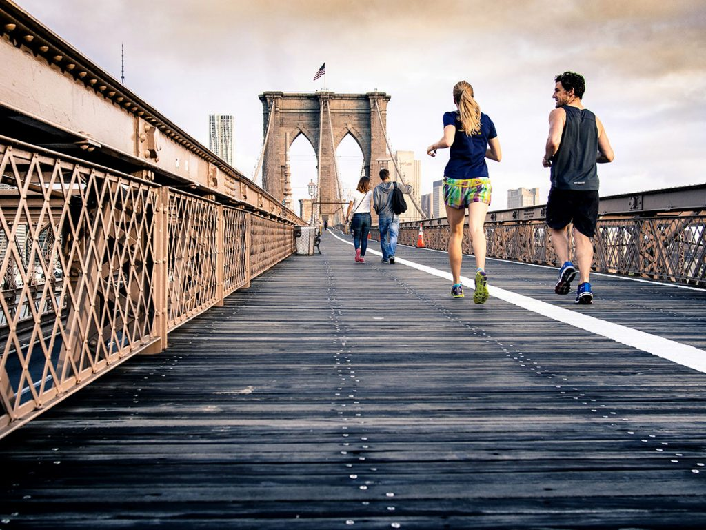 This man and woman running on a bridge could benefit from sports massage therapy.