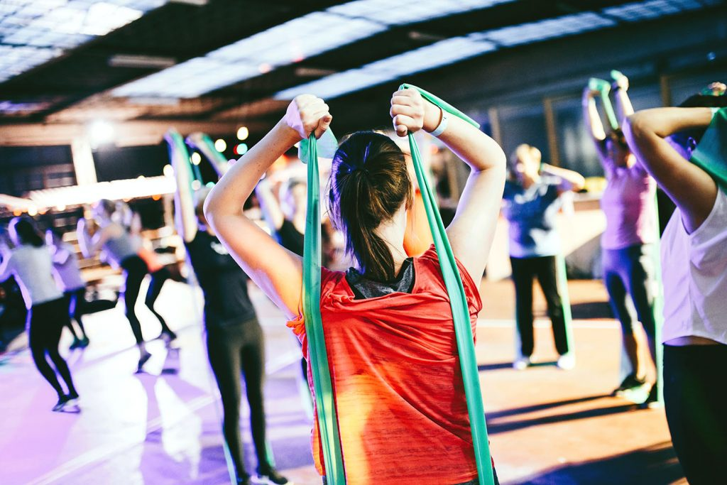 This woman exercising with bands may not compete, but there are benefits to sports massage therapy for her.